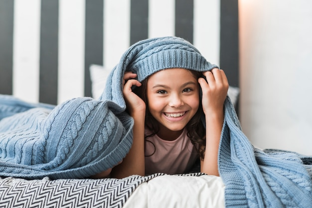 Portrait of a smiling girl lying with her brother under the blanket on bed