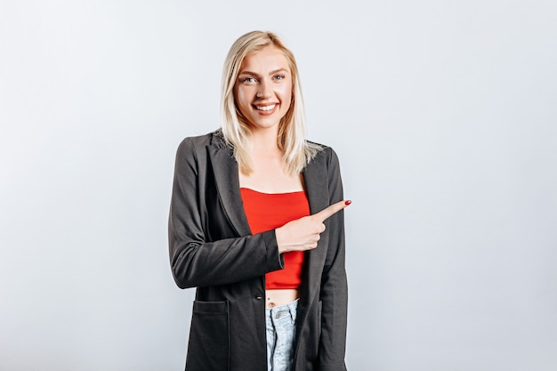 Portrait of a smiling girl pointing finger up at copy space. a woman points to an idea, a place for advertising. positive blonde.