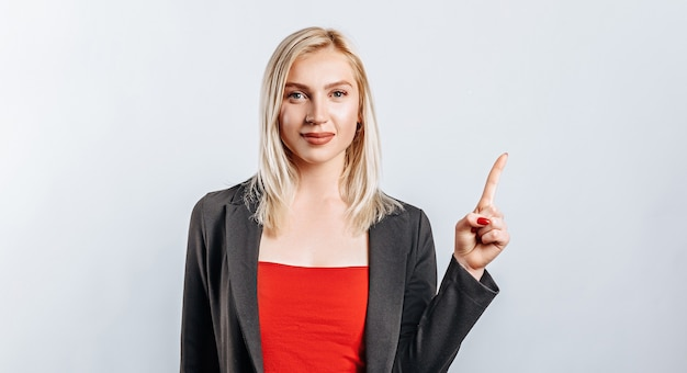 Portrait of a smiling girl pointing finger up at copyspace isolated on a white background. a woman points to an idea, a place for advertising. positive blonde.