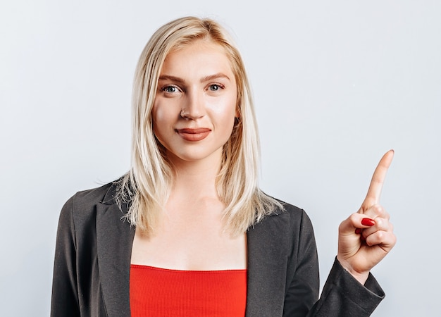 Portrait of a smiling girl pointing finger up at copyspace isolated on a white background