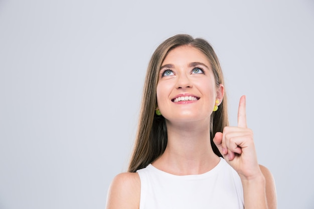 Portrait of a smiling girl pointing finger up at copyspace isolated