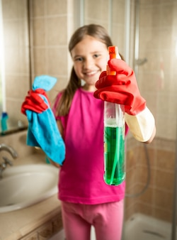 Portrait of smiling girl posing with cloth and cleanser spray at bathroom
