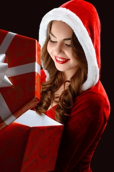 Portrait of smiling girl in the red suit,opening a gift for new year