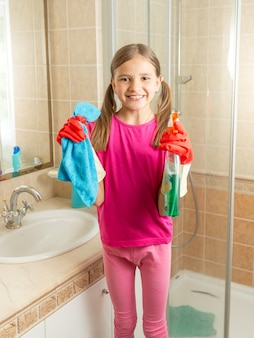 Portrait of smiling girl in rubber gloves cleaning bathroom with cloth and spray
