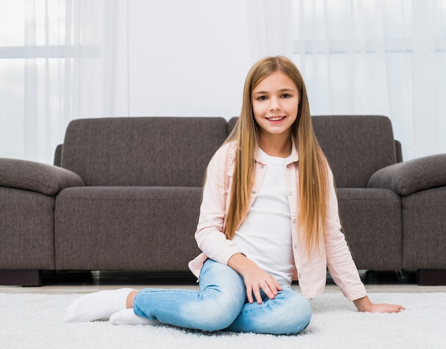 Portrait of smiling girl sitting on carpet in front of sofa looking to camera
