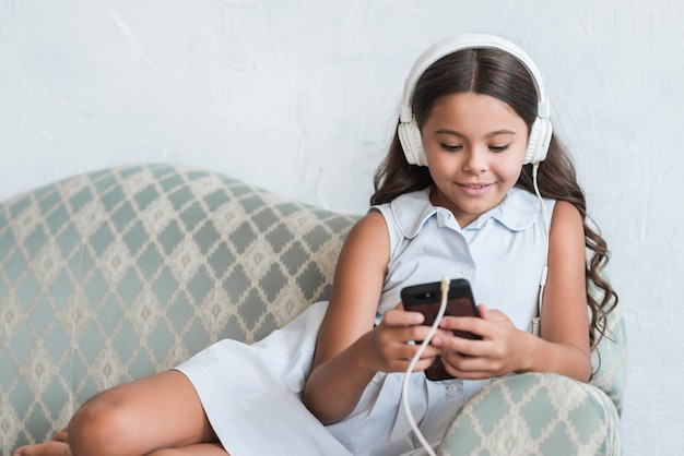 Portrait of a smiling girl sitting on sofa using mobile phone with headphone on her head