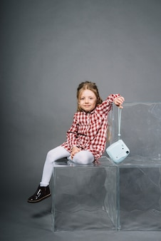 Portrait of a smiling girl sitting on transparent blocks holding retro instant camera in hand