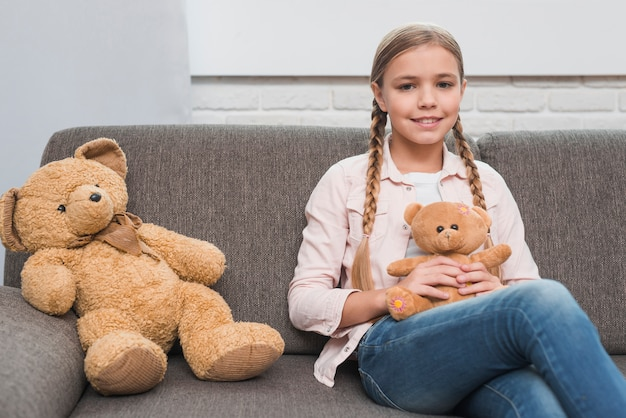 Portrait of a smiling girl sitting with small teddy bear on gray sofa
