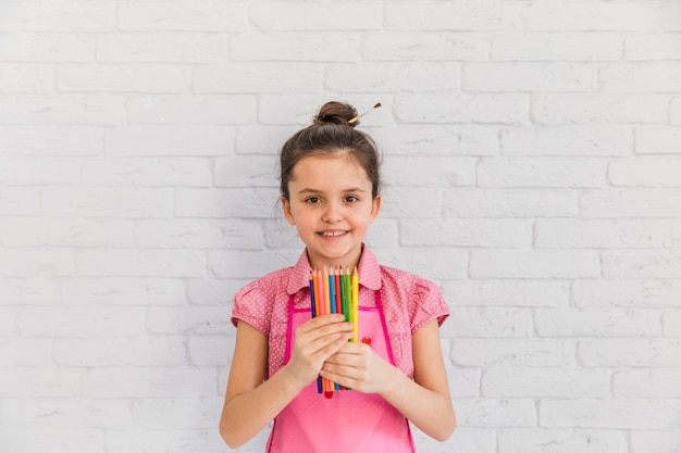 Portrait of a smiling girl standing against white brick wall holding colored pencils in hand