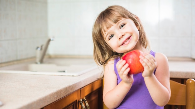 Portrait of a smiling girl standing in kitchen holding fresh red apple