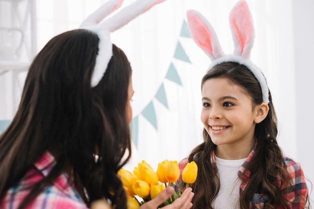 Portrait of a smiling girl wearing bunny ears looking at her mother holding yellow tulips
