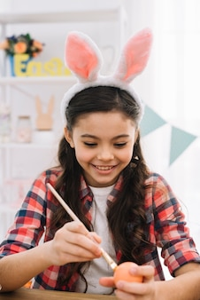Portrait of a smiling girl wearing bunny ears painting easter egg with brush