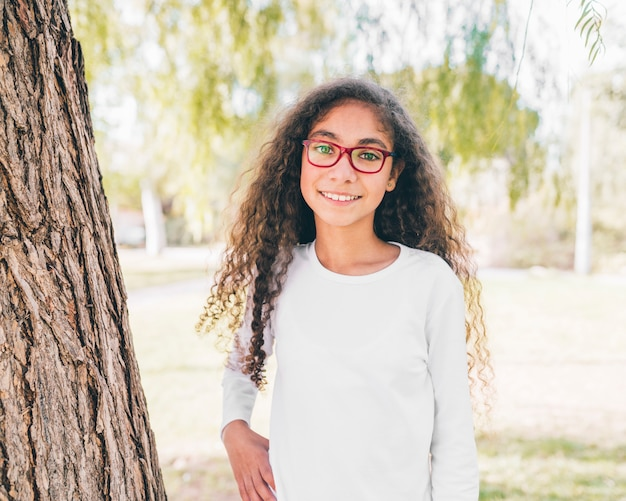 Portrait of a smiling girl wearing red glasses looking at camera