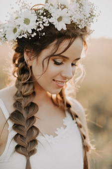 Portrait of smiling girl in white dress with floral wreath and braids in summer at sunset in the field
