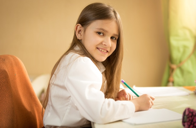 Portrait of smiling girl in white shirt sitting behind desk and doing homework