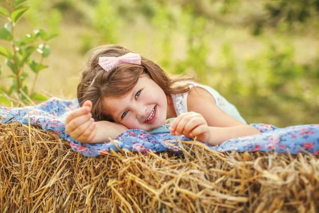 Portrait of a smiling girl with dark long hair lying on a haystack in summer