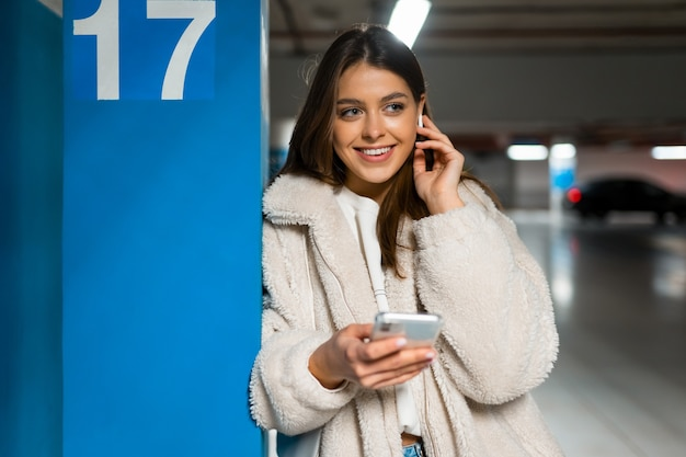 Portrait of smiling girl with phone in hands