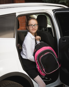Portrait of smiling girl with school bag getting out of the car