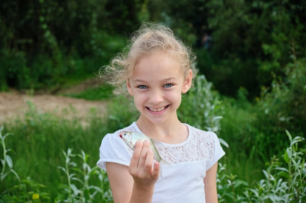 Portrait of a smiling girl with a silver fish in her hands on the space of green nature.