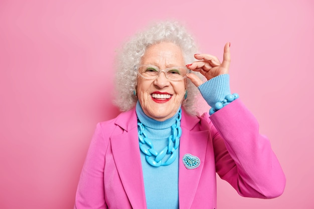 Portrait of smiling good looking senior lady keeps hand on rim of spectacles wears fashionable clothes happy to hear something pleasant has glad expression. age old people fashion and style.