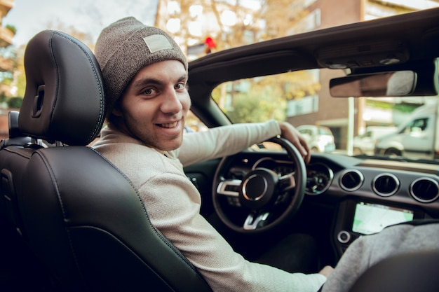 Portrait of smiling guy driving car