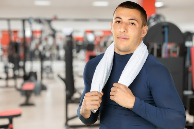 Portrait of a smiling guy at the gym to stay fit and having defined muscles