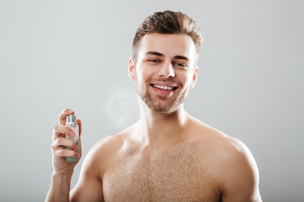 Portrait of a smiling half naked man spraying perfume