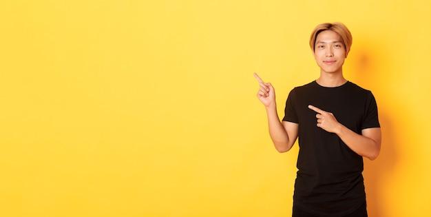 Portrait of smiling handsome asian man in black tshirt pointing fingers upper left corner showing lo...