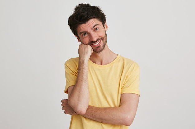 Portrait of smiling handsome bearded young man wears yellow t shirt looks happy and keeps hands folded isolated on white