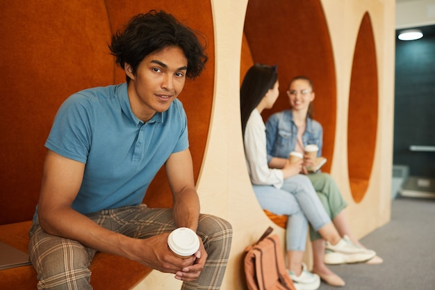 Portrait of smiling handsome dark-skinned boy with disheveled hair sitting in campus lobby and drinking coffee
