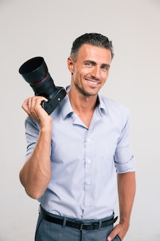 Portrait of a smiling handsome man holding camera isolated