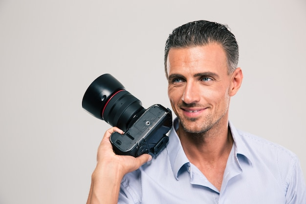 Portrait of a smiling handsome man holding camera and looking away isolated