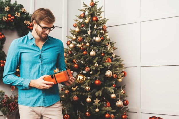 Portrait of smiling handsome man holding gift. sexy bearded male posing near christmas tree with present.