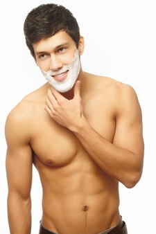 Portrait of smiling handsome man shaving