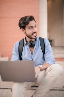Portrait of a smiling handsome man with laptop looking away