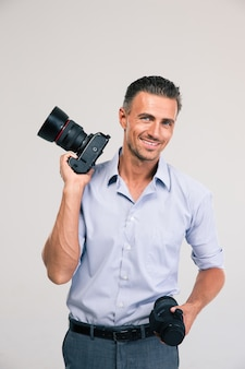 Portrait of a smiling handsome photographer holding camera
