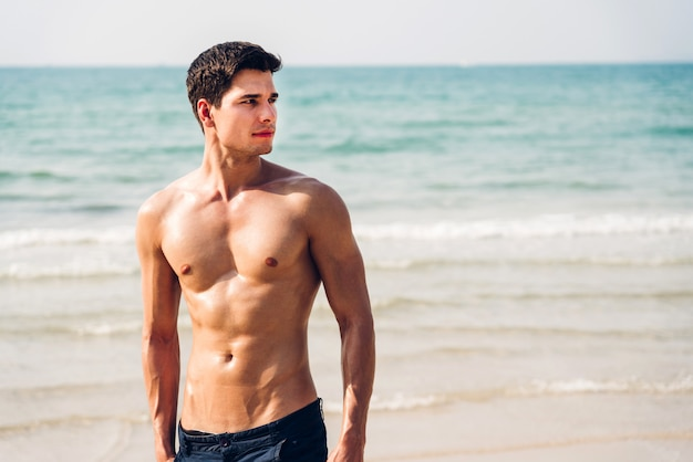 Portrait of smiling handsome sexy man showing muscular fit body standing