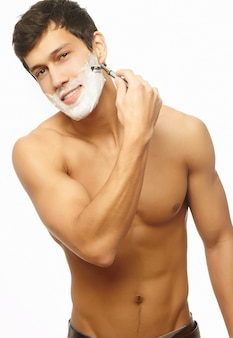 Portrait of smiling handsome successful man shaving