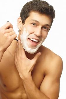 Portrait of smiling handsome successful man shaving