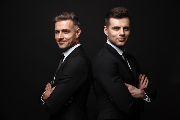 Portrait of smiling handsome two businessmen dressed in formal suit posing at camera back to back isolated over black wall