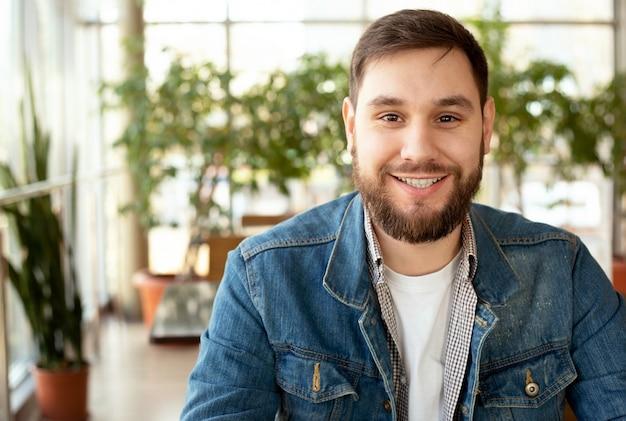窓の近くの現代の企業環境でひげとハンサムな若い男を笑顔の肖像画。カジュアルな服装でジーンズのジャケットのオフィスでスマートな男。カフェで笑っている魅力的なビジネスマンフリーランサー。