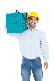 Portrait of a smiling handyman in hard hat carrying a toolbox