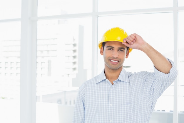 Portrait of a smiling handyman wearing a yellow hard hat