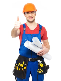 Portrait of smiling handyman with tools and paper showing thumbs up sign   isolated on  white background