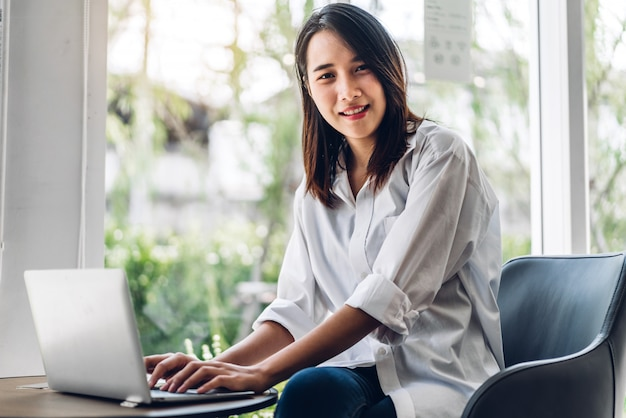 Portrait of smiling happy beautiful asian woman relaxing using laptop computer while sitting on sofa.young hipster girl freelancer working and thinking with new ideas in cafe