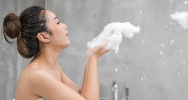 Portrait of smiling of happy beautiful pretty asian woman clean fresh healthy white skin enjoy relaxing taking shower and bath with soap bubble foam on hand in bathtub at the bathroom