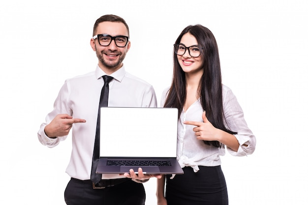 Portrait of a smiling happy business couple pointing at blank screen laptop computer while standing and looking at camera isolated over white background
