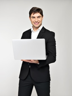 Portrait of smiling happy businessman with laptop in black suit