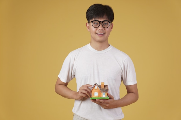 Portrait of smiling happy cheerful young asian man dressed casually with home house model isolated. real estate purchase concept