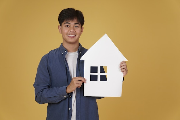 Portrait of smiling happy cheerful young asian man dressed casually with home house paper cutout isolated. real estate purchase concept